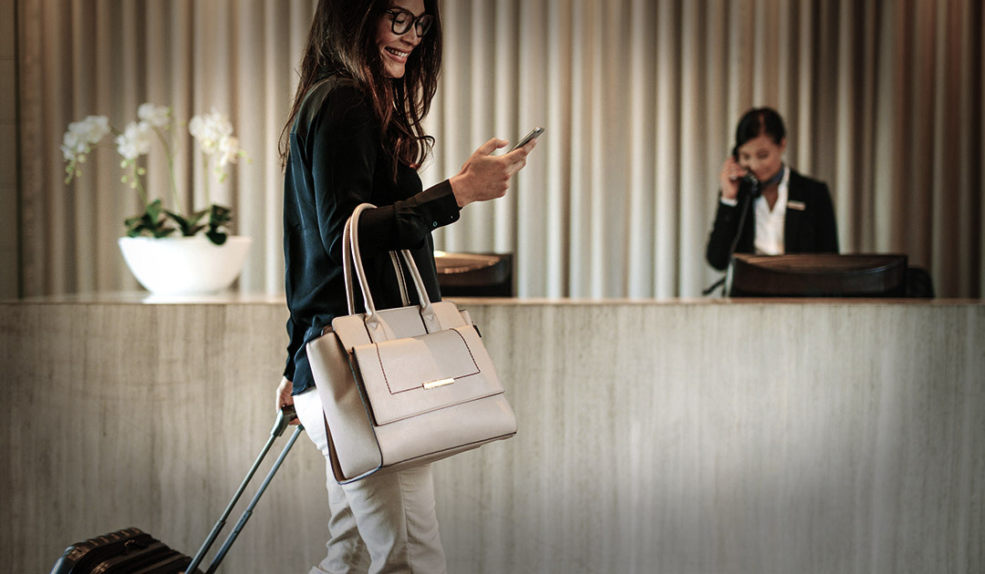 ​Women checking into her hotel, following tips for preventing travel fraud.